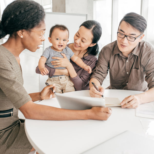 Family with small child looking over documents with another woman