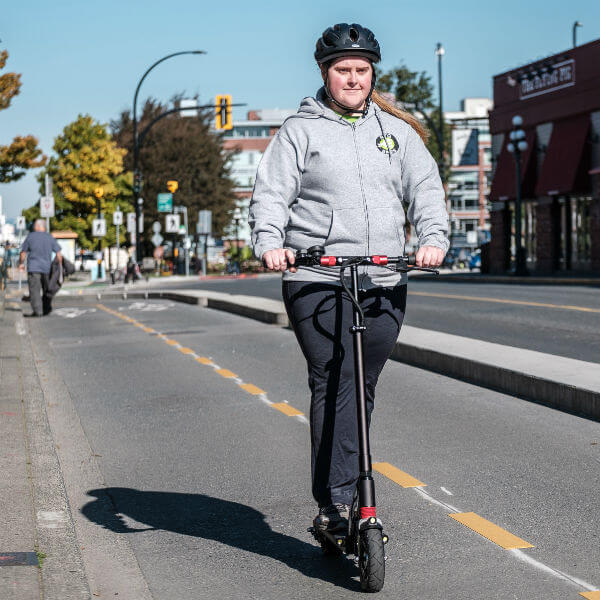 woman riding electric scooter in bike lane
