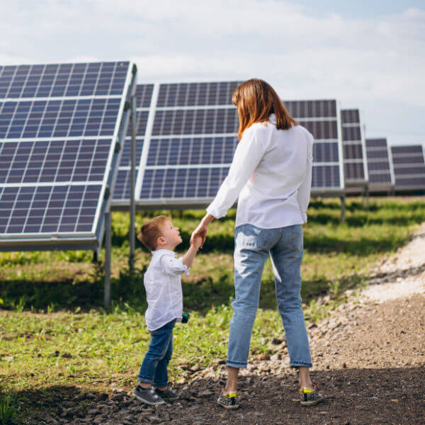 Mother and son stand on a path in a field full of solar powers