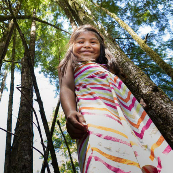 Smiling Indigenous girl surrounded by forest