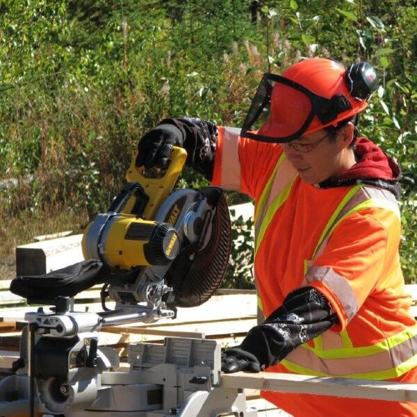 Worker with helmet, safety vest, safety glasses and ear protection uses chop saw to cut wood